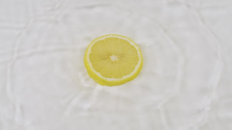 Fall of yellow slice of lemon in white water. Slow motion Live Action
