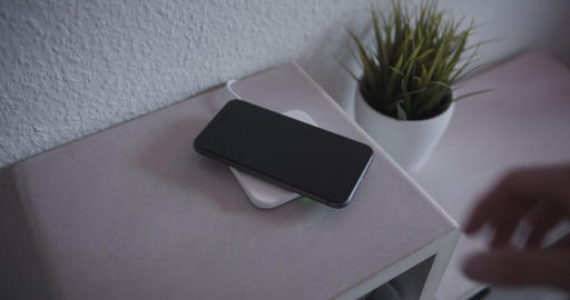 Smartphone being picked up from wireless charging pad Live Action
