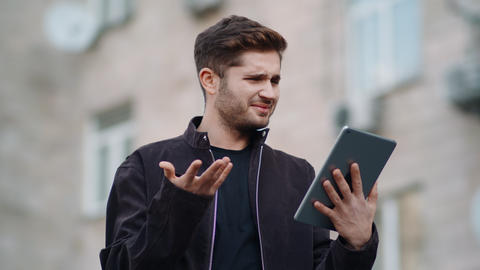 Surprised man looking tablet screen outside. Cheerful guy reading message tablet Live Action