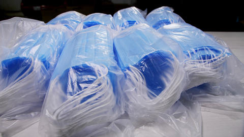 plastic bags with protective masks on table and inside box Live Action