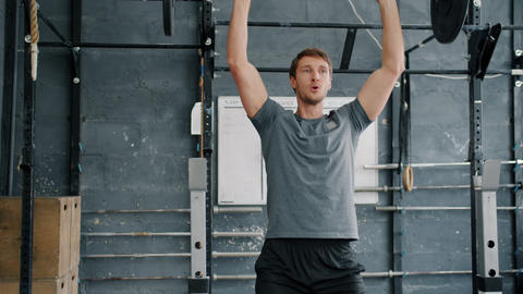 Slow motion of handsome young sportsman lifting barbell training in gym alone Live Action
