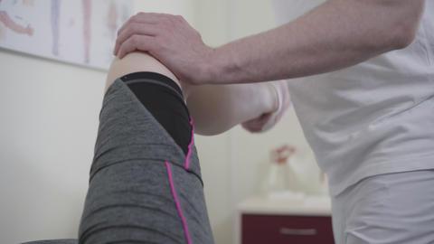 Unrecognizable traumatologist checking injury of sportswoman. Male Caucasian Live Action