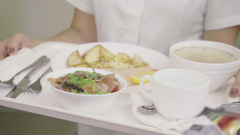 Close-up of tray with hospital food in female hands. Unrecognizable Caucasian Live Action