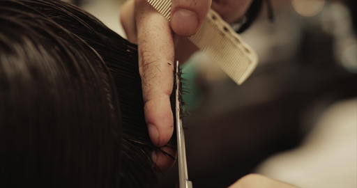 Hair care. Men's haircut in a barbershop. Haircut with scissors Live Action