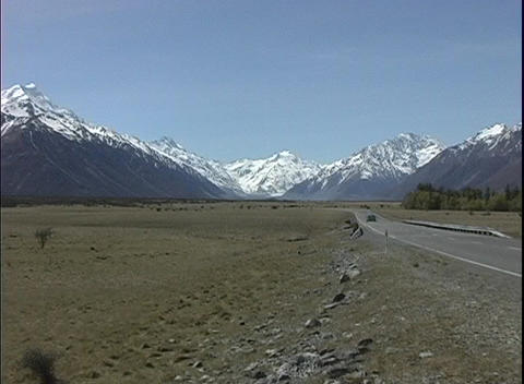 The camera zooms in on snow-capped Mt. Cook in New Zealand as a car approaches from the distance Footage