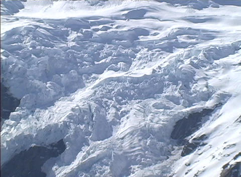 Camera zooms in on snowy, glacier covered mountain peaks... Stock Video Footage