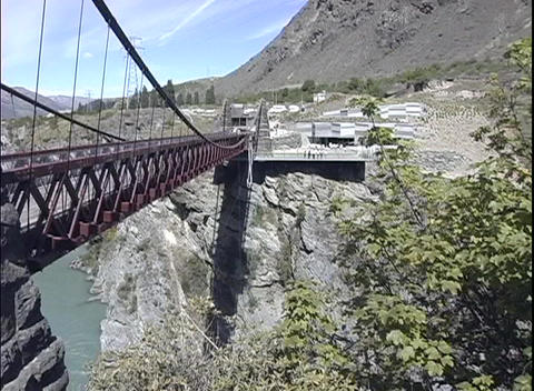 A long-shot of a man bungee jump off a steel suspension bridge in New Zealand Footage