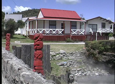 Houses And Carved Icons Exist Side-by-side Near A Geothermal Area In New Zealand stock footage