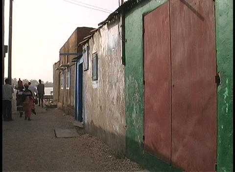 A medium shot of people walking through an alley in a slum in West Africa Live Action
