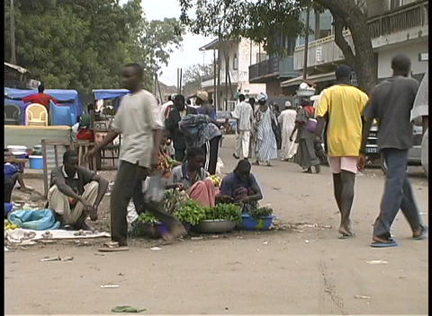 Passersby check out sidewalk vendors at an open-air market in Goree, West Africa Footage