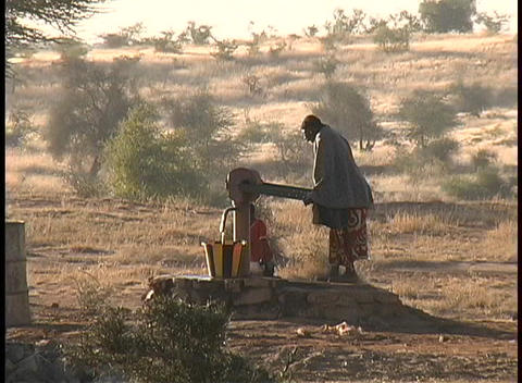 Native South African woman struggles to pump water from a... Stock Video Footage