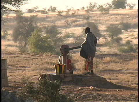 Native South African woman struggles to pump water from a well Footage