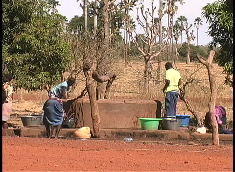 People wash clothes and haul water from a well in Mali,... Stock Video Footage