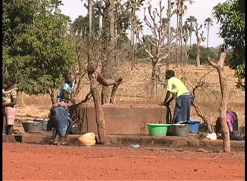People wash clothes and haul water from a well in Mali, West Africa Footage