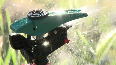 Close-up rack focus on a sprinkler spraying water in Oak View, California Footage