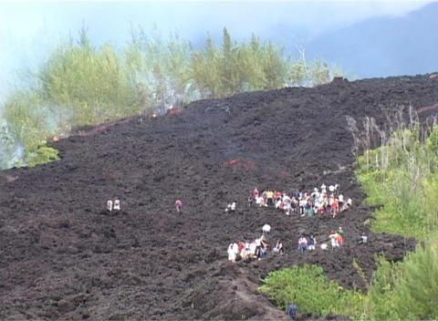 Tourists walk across hardened lava on Reunion Island Stock Video Footage
