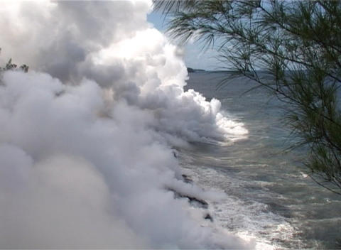 Lava flows from a volcano into the sea at Reunion Island, causing huge clouds of steam Footage