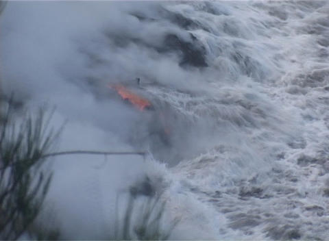 Ocean waves crash in on a lava flow on a Pacific Ocean island Footage