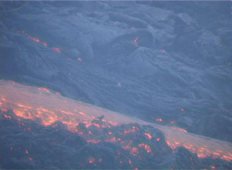 Lava flows down the side of a volcano Footage