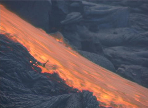 Red hot lava flows down a mountainside during a volcanic... Stock Video Footage