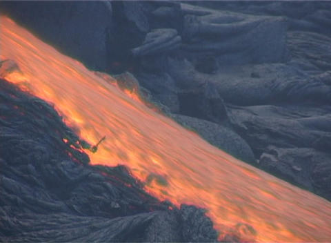 Red hot lava flows down a mountainside during a volcanic eruption Footage