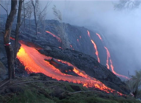 Red hot lava flows over a volcanic cone during an eruption in a primeval scene Footage