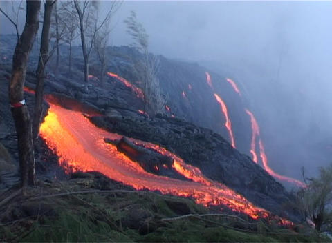 Red hot lava flows over a volcanic cone during an... Stock Video Footage