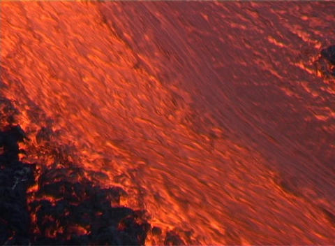 A wall of red hot lava flows down the slopes of a volcano Stock Video Footage