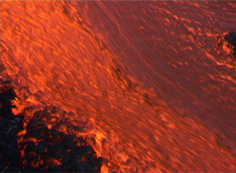 A wall of red hot lava flows down the slopes of a volcano Footage