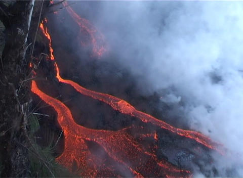 Rivers of red hot lava flow down the slopes of a volcano with smoke rising Footage