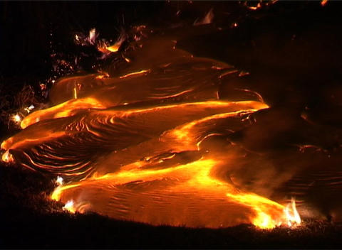 Flames lick around the edges of a lava flow following a... Stock Video Footage