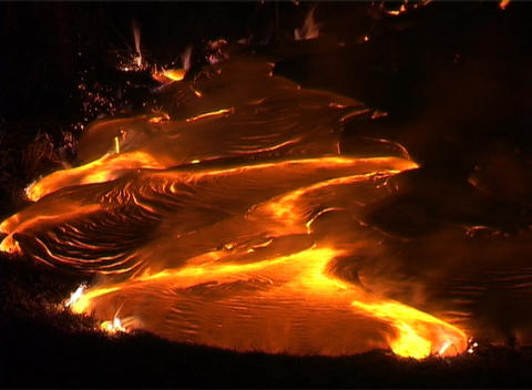 Flames lick around the edges of a lava flow following a volcanic eruption Footage