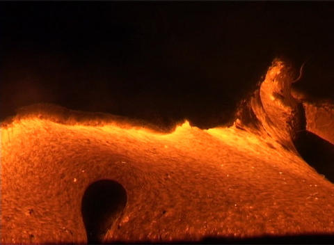 Molten lava oozes from a volcano, erupting eerily into... Stock Video Footage