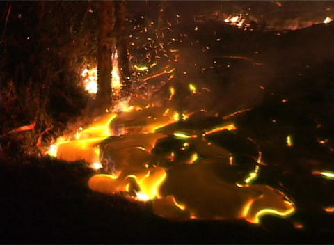 Lava oozing from a volcano surrounds trees and flows into a road as flames burn and sparks fly Footage