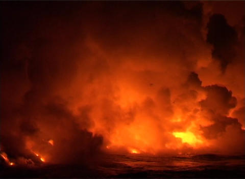 Clouds of flame, smoke, and steam billow when lava flows into the ocean as birds fly high above th Footage