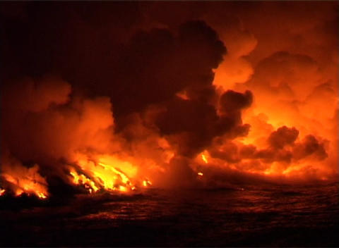 Clouds of flame, smoke, and steam billow into the night sky when molten lava flows into the ocean Footage
