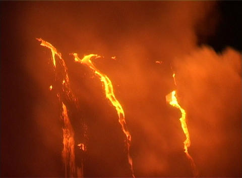 Rivers of lava flow down a volcanic slope while smoke rises Stock Video Footage