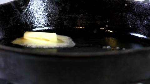 a tab of margarine containing trans fats melts in a hot... Stock Video Footage
