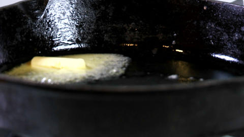 a tab of margarine containing trans fats melts in a hot skillet Footage