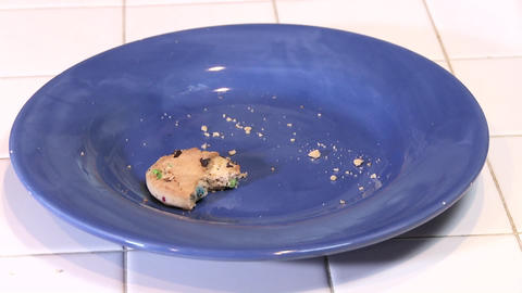 A half eaten cookie on an empty plate with crumbs Footage