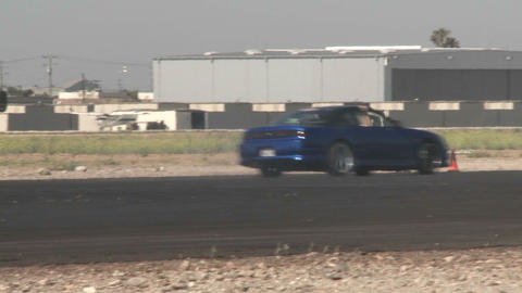 the camera follows a blue car as it glides through a drifting course at Camarillo Airport in Camaril Footage