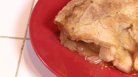 A fresh baked slice of apple pie is ready to eat on a red plate Footage