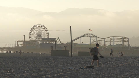 A man walks in the sand in front of Santa Monica Pier in Santa Monica California Footage