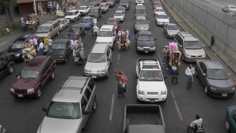 Vendors hock their goods as cars wait to cross back into... Stock Video Footage