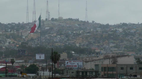 the Mexican flag is seen waving above downtown Tijuana... Stock Video Footage