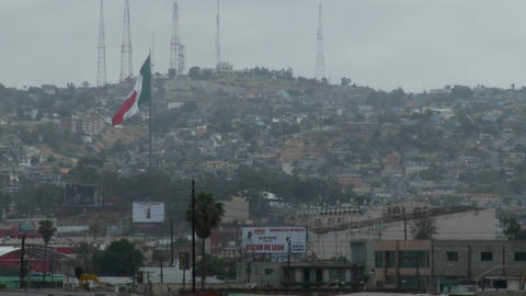 the Mexican flag is seen waving above downtown Tijuana Mexico Footage