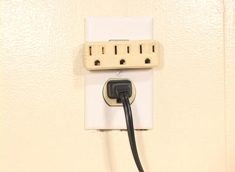 Too many electrical cables are plugged into one outlet in a shot symbolizing the overuse of energy Live Action