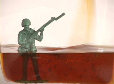 Oil fills up a container drowning a plastic soldier, symbolizing the nation and military drowning i Footage