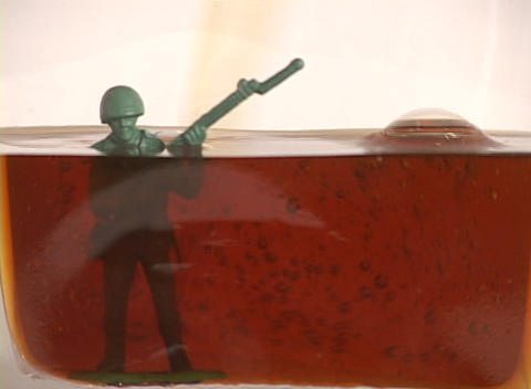 Oil fills up a container drowning a plastic soldier,... Stock Video Footage