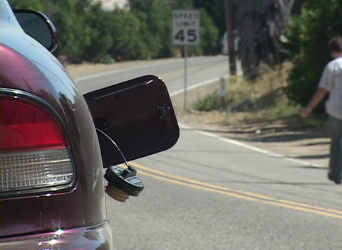 A man hitchhikes down a highway after his car runs out of... Stock Video Footage